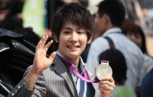 加藤凌平がスーツ姿で銀メダルを持って手を振っている画像
