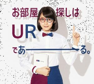 吉岡里帆が赤と青の丸メガネ,蝶ネクタイ,スカートで人差し指を上の方に向けているURであーるのCMの画像