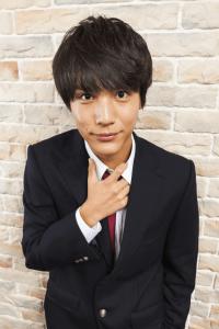 中川大志が学生服(ブレザー)を着てネクタイを緩めようとして手を結び目に添えている画像