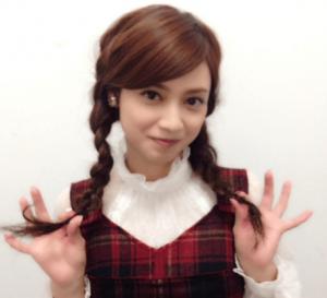 平愛梨がチェックのワンピースを着て三つ編みを両手で摘んでこっちを見ている画像
