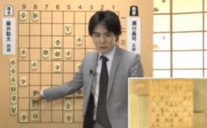 佐々木勇気五段がスーツ姿で将棋の解説をしている写真の画像