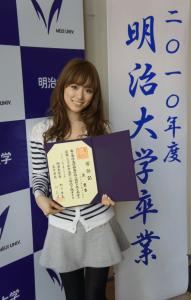 泉里香が明治大学文学部英米文学科を卒業して卒業式で卒業証書を持ってこっちを見て写真を撮っている画像